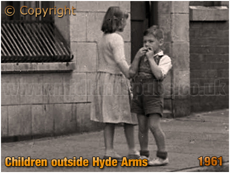 Boy and girl playing outside the Hyde Arms on the corner of Clark Street and Hyde Street at Ladywood in Birmingham [1961]